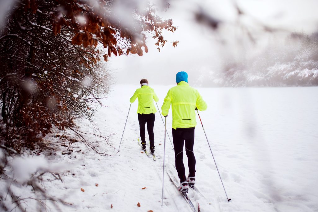 Active senior couple cross-country skiing. Winter time. Rear view.